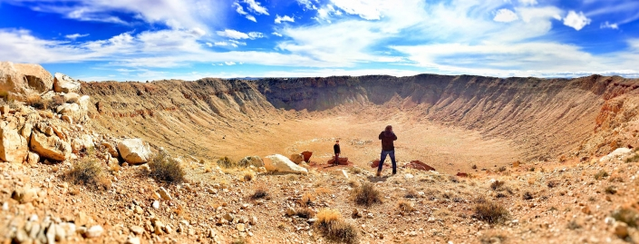 Panoramic landscape of young man getting his picture taken at Meteor Crater Natural Landmark in Winslow, Arizona. Also known as Barringer Crater by Phoenix commercial photographer Jason Koster.