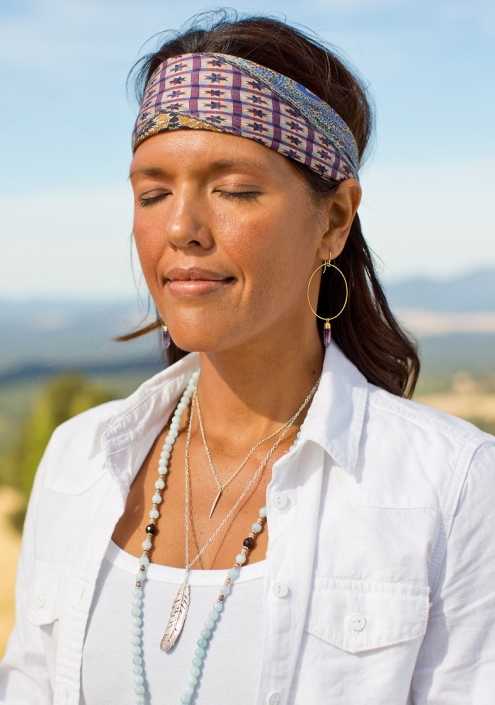 Peaceful woman wears hoop earrings and a variety of necklaces with bandana and eyes closed of grassy field of Flagstaff, Arizona.