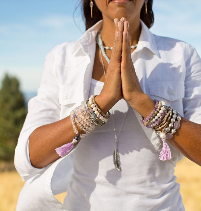 Lifestyle photography of praying woman wearing various mala and beaded bracelets stands with palms together in Flagstaff, Arizona. Image by commercial photographer Jason Koster.