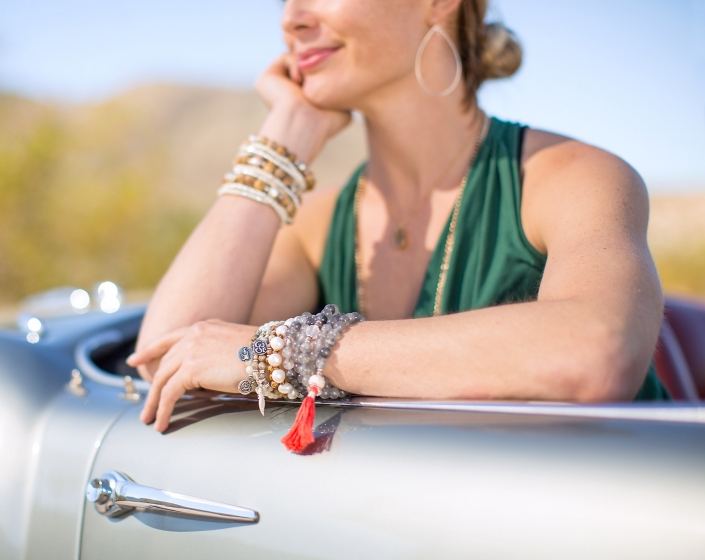 Lifestyle photography of fashionable woman wearing gold teardrop earrings and a variety of bracelets with charms OM, Lotus, Ganesh. Image by commercial photographer Jason Koster.