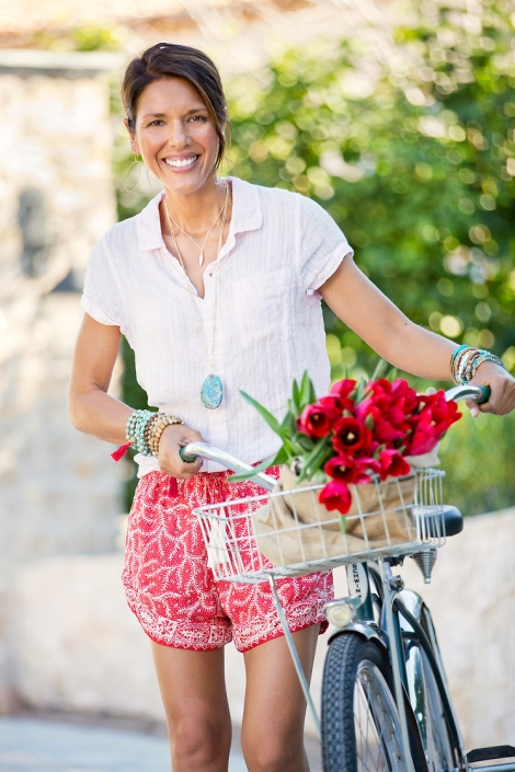 Happy woman wears a variety of beaded bracelets, gold chain necklaces, Agate and gold hoop earrings for catalog photography while walking Schwinn bicycle with red bundle of tulips in the basket.