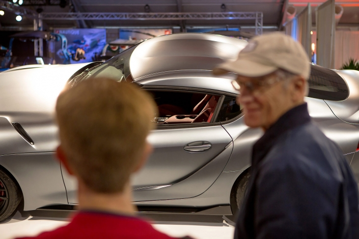 Editorial photography of father looking at son looking at 2019 Toyota Supra at Barrett-Jackson. Image by Phoenix commercial photographer Jason Koster.