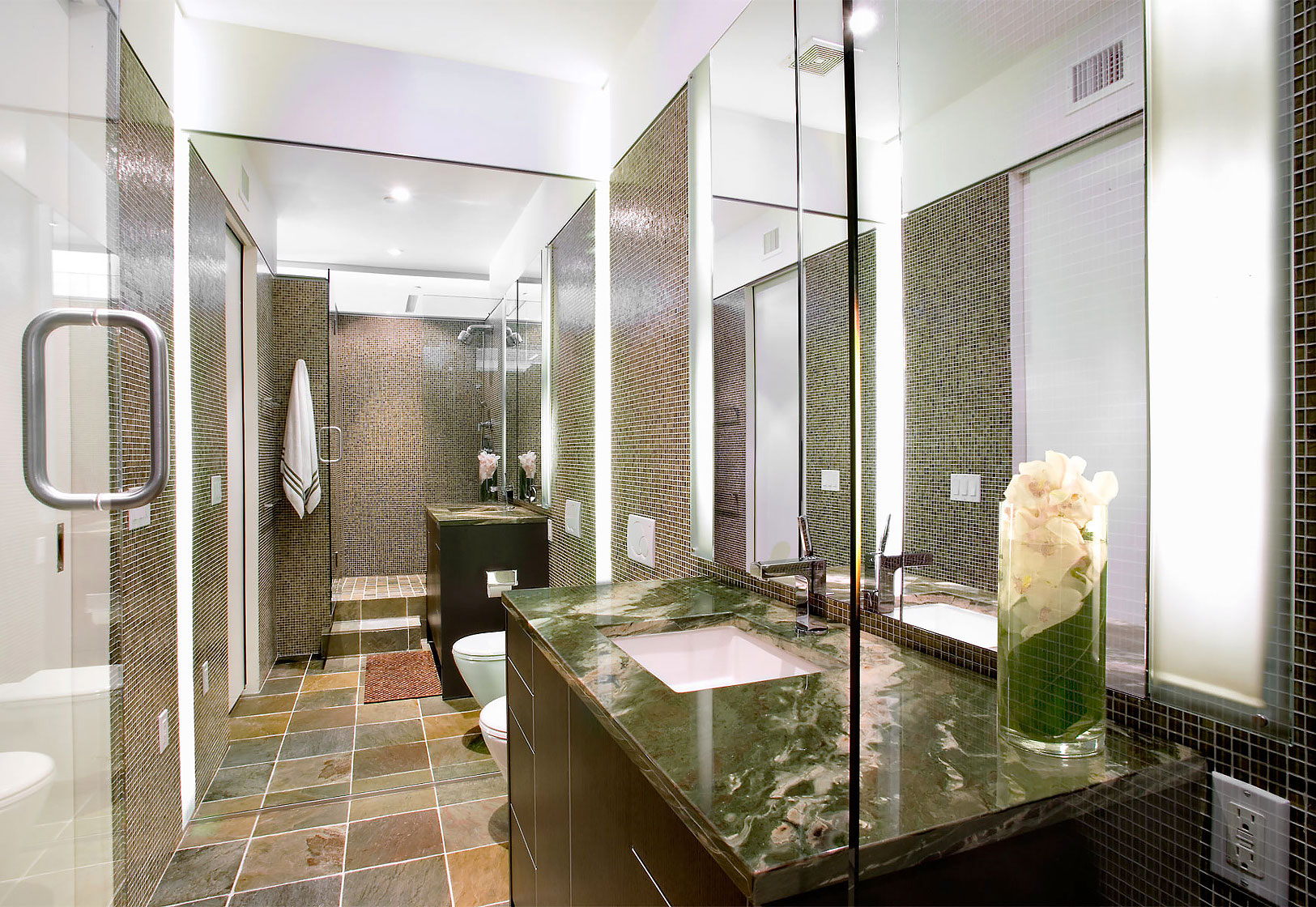 Editorial photography of modern style bathroom with mirror wall, glass shower and green granite countertops by Phoenix commercial photographer Jason Koster.