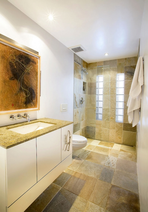 Editorial photography architectural interior of modern bathroom with stone floor, glass shower and rock climber figure cabinet handle by Phoenix commercial photographer Jason Koster.