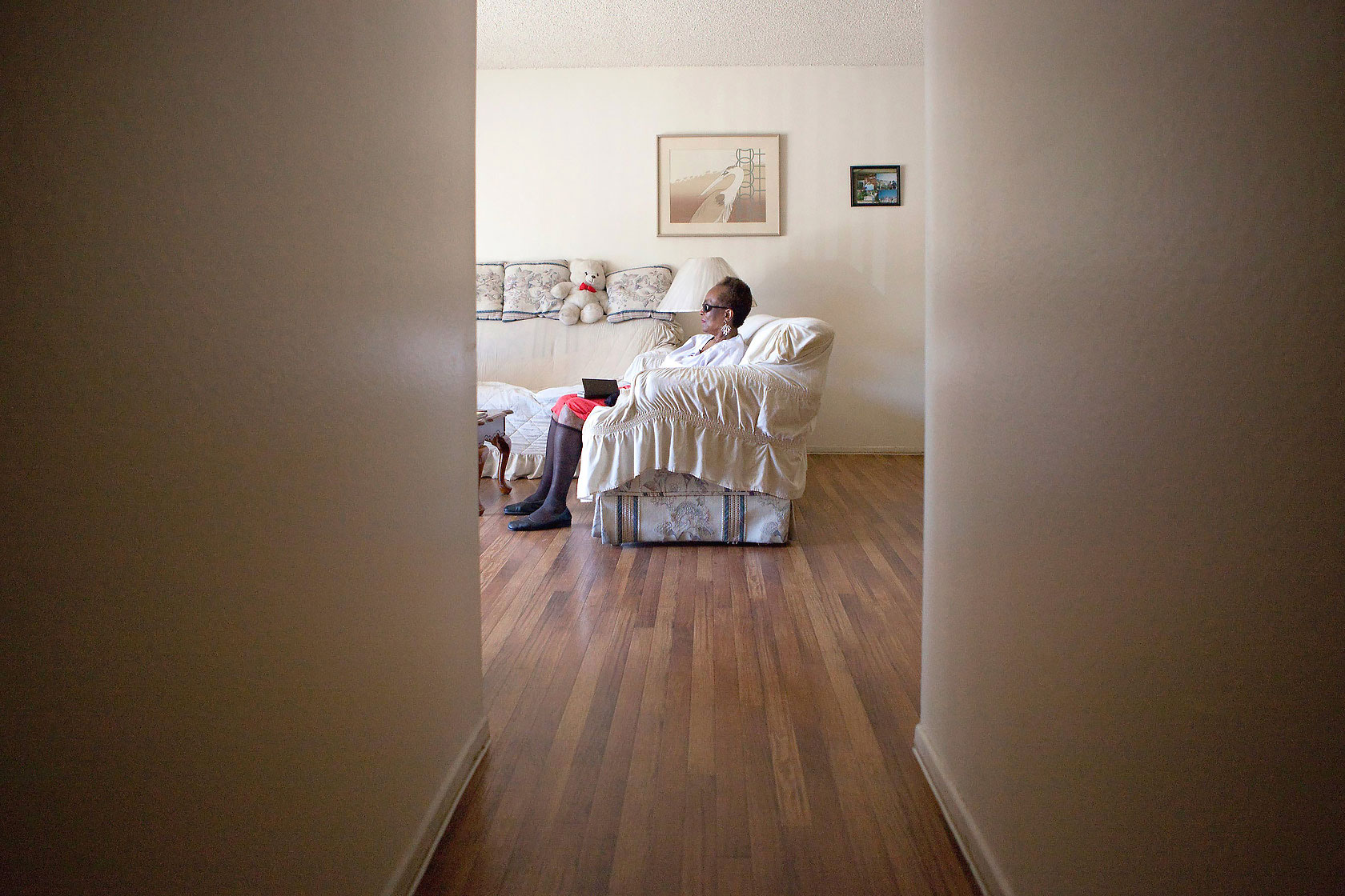 Editorial photography of a visually impaired woman sits on couch at the end of the hall waiting for assistance. Image by Phoenix commercial photographer Jason Koster.