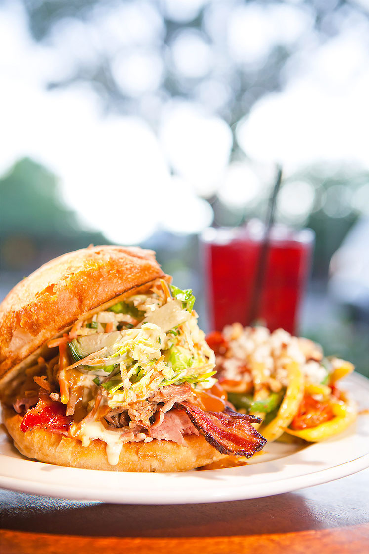 Editorial photography of messy sandwich with bacon next to red drink outside by Phoenix commercial photographer Jason Koster.