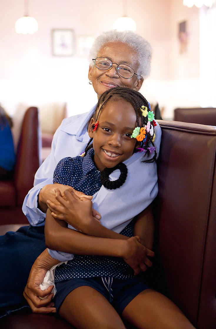 Editorial portrait of smiling grandma hugs smiling granddaughter with barrettes. Image by Phoenix commercial photographer Jason Koster