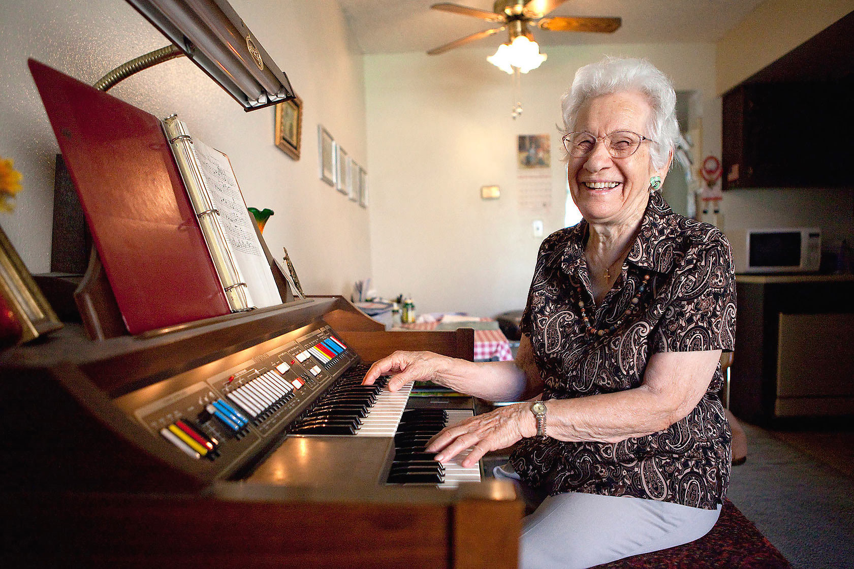 Editorial photography of grandma laughs while playing multi manual organ by Phoenix commercial photographer Jason Koster.