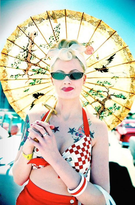 Editorial photography of vintage pinup woman in sunglasses with parasol and tattoos at car show by Phoenix commercial photographer Jason Koster