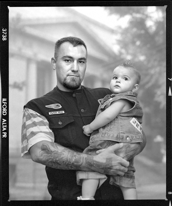 Editorial photography of motorcycle club member with son stands outside of Prescott Arizona Courthouse by Phoenix commercial photographer Jason Koster.