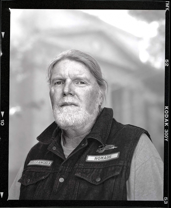 Editorial portrait black and white portrait of motorcycle club member outside courthouse in Prescott Arizona.