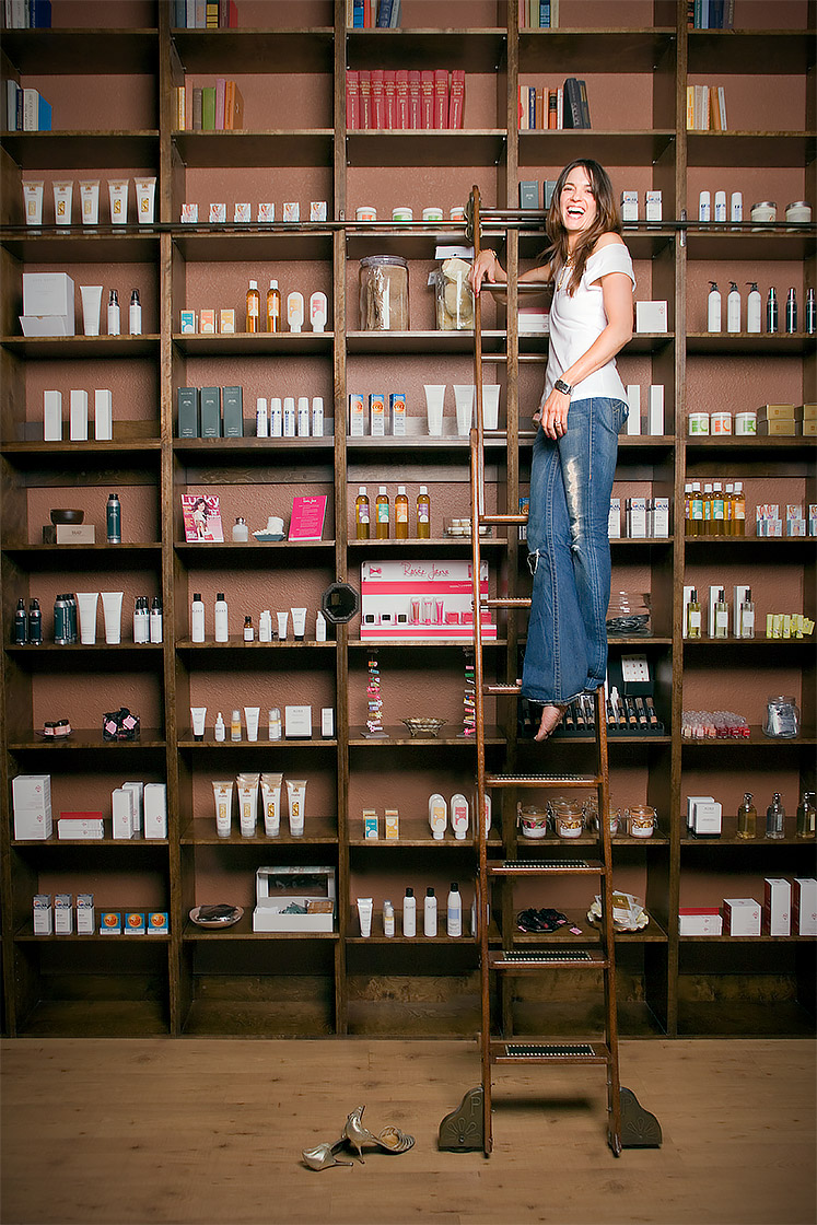Editorial portrait of a woman in front of a wall of beauty products at the top of a book ladder with no shoes and laughing. Shot for Vegas Magazine by Phoenix editorial photographer Jason Koster.