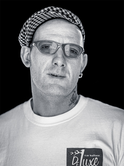 Editorial photography style natural light portrait in black and white of rockabilly culture guy with tweed hat, funky glasses, neck tattoo, earring and DeLuxe Car Kulture t-shirt.