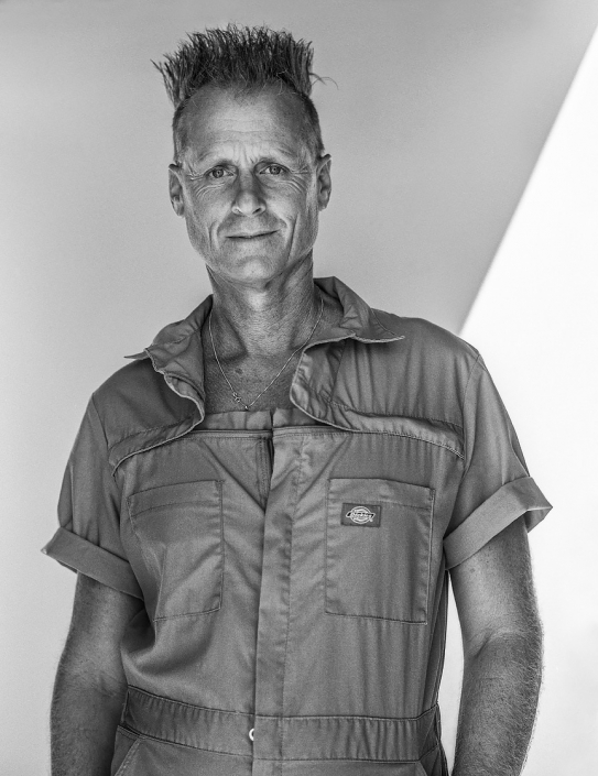 Editorial photography style natural light portrait in black and white of rockabilly culture guy in Dickies brand coveralls.