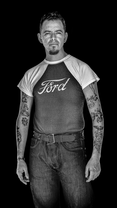 Natural light portrait in black and white of rockabilly guy with tattoos wearing a Ford T-shirt. Shot by Phoenix commercial photographer Jason Koster.