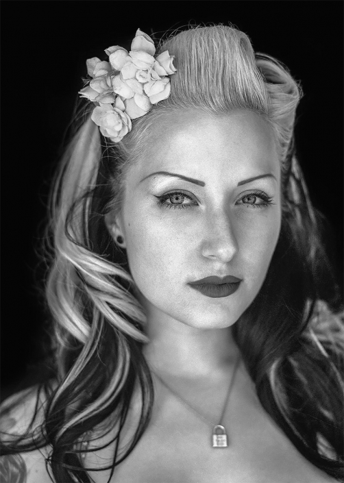 Editorial photography style natural light portrait in black and white of beautiful young woman with flowers in her hair and lock necklace around her neck.