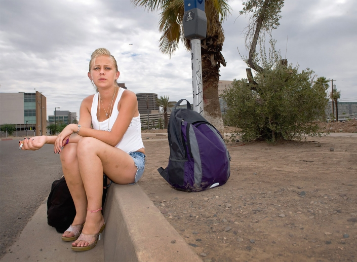 Editorial photography of bruised homeless young woman with two backpacks sits on the curb in downtown Phoenix smoking. Image by Phoenix commercial photographer Jason Koster.