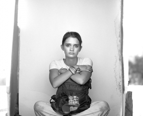Editorial photography of homeless young woman sits on the ground with her backpack in a portrait box by Phoenix commercial photographer Jason Koster.